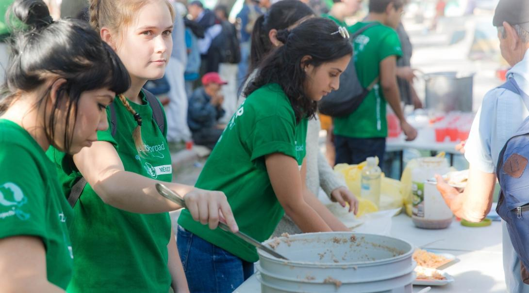 Female International Development Interns serve food at a shelter for immigrants at their work placement in Mexico.